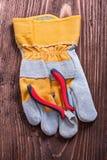 Plastikowi nippers i ochronna rękawiczka na drewnie wsiadają Zdjęcia Stock