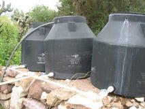 Plastikowi zbiorniki wodni suszy na skalistym tle Zdjęcie Stock