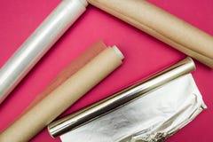 Plastikowy opakunek, aluminiowa folia i rolka pergaminowy papier na różowym tle, obraz stock