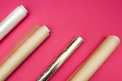 Plastikowy opakunek, aluminiowa folia i rolka pergaminowy papier na r??owym tle, zdjęcia stock