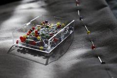 Plastikowy przejrzysty pudełko z szyć barwione igły na tle szara tkanina Obrazy Royalty Free