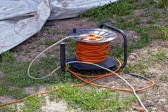 Plastikowy przewoźnik z różyczkami i pomarańczowy kabel na zielonej trawie zdjęcia royalty free