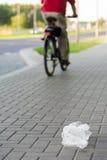 Plastikowy worek rzucający bicyclist na ulicie Zdjęcia Stock