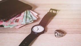Plastikowy zegarka, srebra pieniądze w Brown portflu na, ringowy i Tajlandzki Zdjęcie Stock