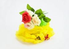 Plastikrosafarbene Blume und Plastiktasche auf weißem Hintergrund Lizenzfreies Stockfoto