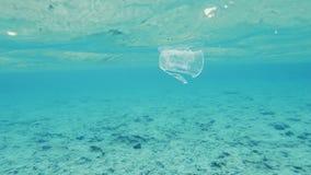 Plastikschale, die das Meer verunreinigt stock footage