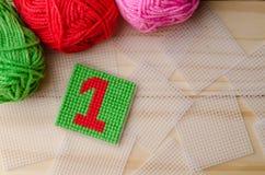 Plastiksegeltuch, handgemacht mit roter Garnzahl auf hölzernem backgro Stockfotos