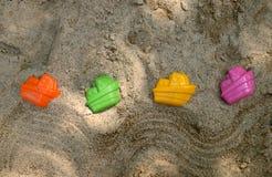 Plastikspielwaren auf mit gelbem Sand Stockbild