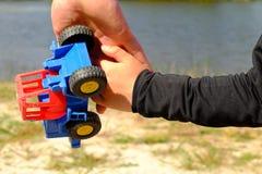 Plastikspielzeuglastwagen des großen Durchlaufs des Vaters Handzur Hand eines kleinen Jungen Hände in den blauen und schwarzen He Lizenzfreie Stockbilder