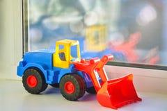 Plastikspielzeugtraktor auf dem Fensterbrett Reflexion im Glas Stockfotografie