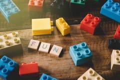 Plastikspielzeugziegelsteine mit Alphabet deckt Wort SPASS auf Holztisch mit Ziegeln lizenzfreies stockbild