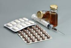 Plastikspritze, Glasampullen mit Medizin und Pillen im blist Stockbilder