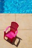 Plastikstuhl und blaues Pool stockfoto