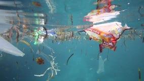 Plastiktaschen und anderer Abfall, die unter Wasser schwimmt stock video