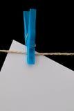 Plastikwäscheklammer, die Weißbuch auf einem Draht hält Lizenzfreie Stockfotografie