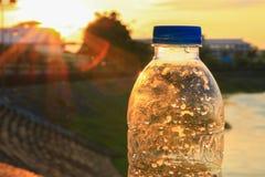 Plastikwasserflasche auf dem Steinboden in einem allgemeinen Park bei Sonnenuntergang, Sonnenaufgangzeit stockfotografie