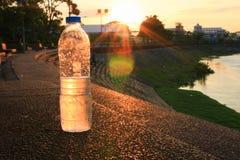 Plastikwasserflasche auf dem Steinboden in einem allgemeinen Park bei Sonnenuntergang, Sonnenaufgangzeit stockbilder