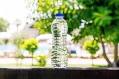 Plastikwasserflasche, die auf einem Sommer, Bäumen und Pool auf einem Hintergrund steht Stockfotografie