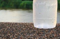 Plastikwasserflasche kühl auf dem Steinparkhintergrund des bodens öffentlich stockbild