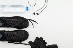 Plastikwasserflasche, schwarze Sportschuhe, Handschuh und Kopfhörer auf weißem Hintergrund stockfotografie