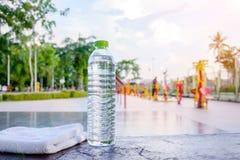 Plastikwasserflasche und weißer Stoff auf Schreibtisch mit laufendem exerci Stockfotografie