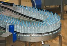 Plastikwasserflaschen auf Förderanlage Stockbilder