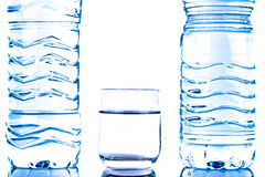 Plastikwasserflaschen mit einem Glas Stockfotografie