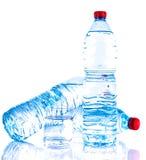 Plastikwasserflaschen mit einem Glas Stockfoto