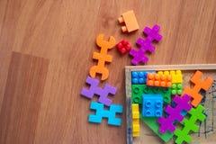 Plastique coloré de jouet sur le fond en bois de plancher Image libre de droits