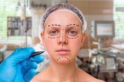 Plastische chirurgie de arts trekt lijnen met teller op geduldig gezicht Stock Foto