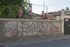 Plastische samenstelling van waterkruiken op de muur met een beeld van een aardewerkworkshop bij de kruispunten van Karaimskaya e stock foto