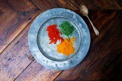 Plat argenté circulaire avec trois épices colorées là-dessus piments t Photographie stock