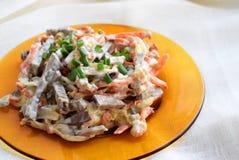 Plat avec de la salade de foie et de légume sur la table Photos stock