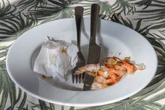 Plat avec des appareils et des queues de cuisson de la crevette Fruits de mer délicieux, déchets images stock