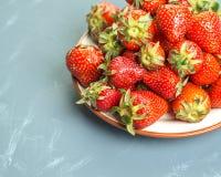 Plat avec des fraises sur un fond bleu-clair Images libres de droits