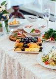 Plat avec des fruits sur la table de dîner Raisins et morceaux de pommes et de poires dans le plat blanc sur la table Images libres de droits