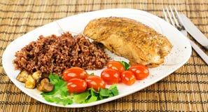 Plat avec la dinde de rôti avec du riz brun et rouge et la cerise entière Image stock