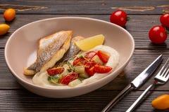 Plat avec la morue frite de poissons, les pommes de terre cuites avec l'aneth, le concombre mariné, le limon et le poivron rouge photos libres de droits