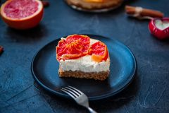 Plat avec le morceau de gâteau au fromage cuit au four avec les tranches rouges de pamplemousse et de fourchette de vintage sur l Photo libre de droits