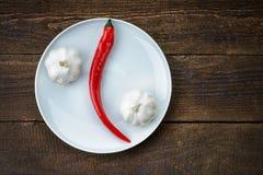 Plat avec le poivre et l'ail de piments d'un rouge ardent Photographie stock libre de droits