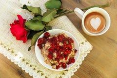 Plat avec le porrige, tasse avec le coffe et rose de rouge sur le tabl approximatif Photographie stock libre de droits