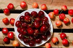 Plat avec les cerises rouges sur la cerise de plats, jaune et rouge en bois, vue supérieure Photo libre de droits