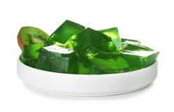 Plat avec les cubes et le kiwi verts en gelée sur le blanc image libre de droits