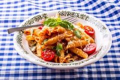 Plat avec les feuilles bolonaises de dessus et de basilic de persil de tomates-cerises de sauce à pene de pâtes sur la nappe bleu Images stock
