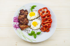 Plat avec les oeufs au plat, le lard et le paprika sur la table en bois Images libres de droits
