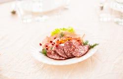 Plat avec les produits carnés découpés en tranches sur la table de fête image stock