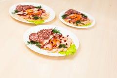 Plat avec les produits carnés découpés en tranches sur la table de fête images stock