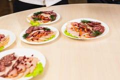 Plat avec les produits carnés découpés en tranches sur la table de fête photographie stock