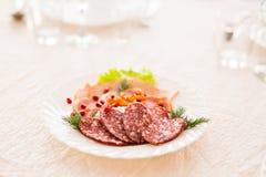 Plat avec les produits carnés découpés en tranches sur la table de fête photo libre de droits