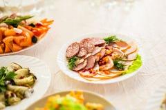 Plat avec les produits carnés découpés en tranches sur la table de fête image libre de droits
